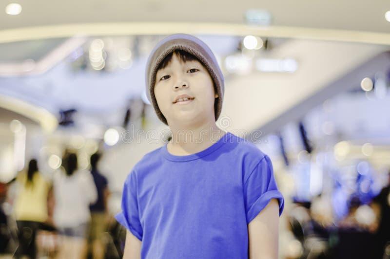 亚裔男孩佩带的帽子穿戴便装,愉快地微笑在购物中心的微笑 免版税库存图片