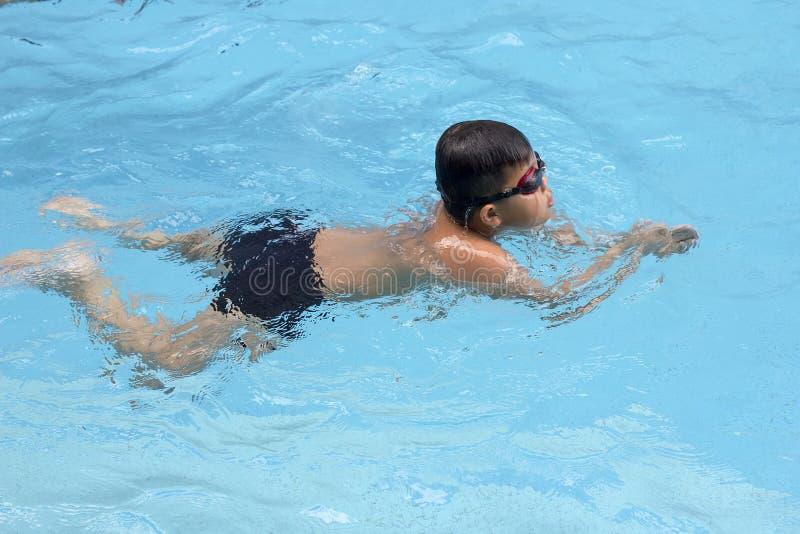 亚裔男孩俯式在游泳池游泳 免版税库存照片