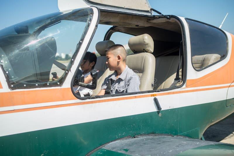 亚裔男孩和女孩在飞机驾驶舱内  图库摄影