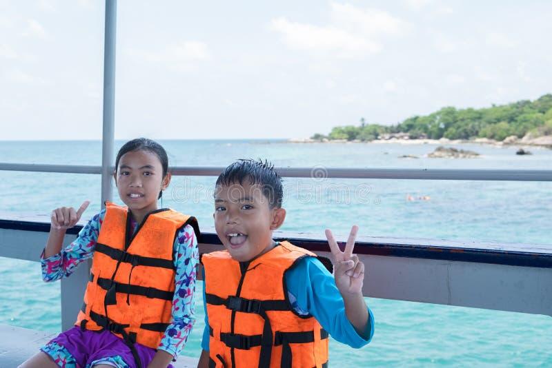 亚裔男孩和女孩画象小船的在海滩 库存照片