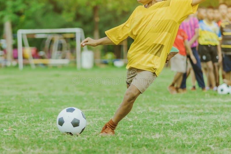 亚裔男孩实践踢球进球 免版税库存图片