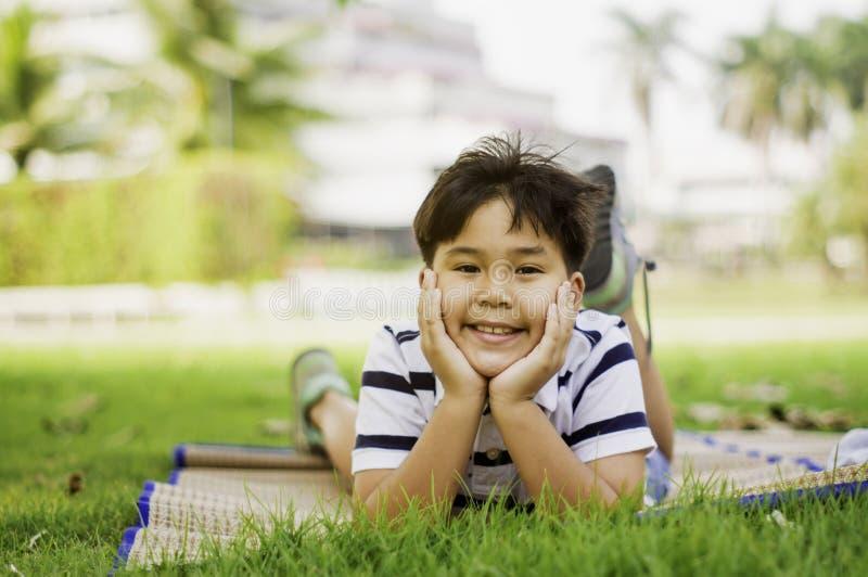 亚裔男孩是在周末放松的心情在公园在早晨阳光下,明亮的童年的概念,学会外面 库存图片