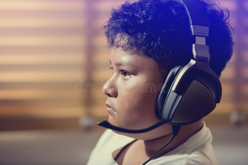 亚裔男孩游戏玩家画象佩带耳机 免版税库存照片