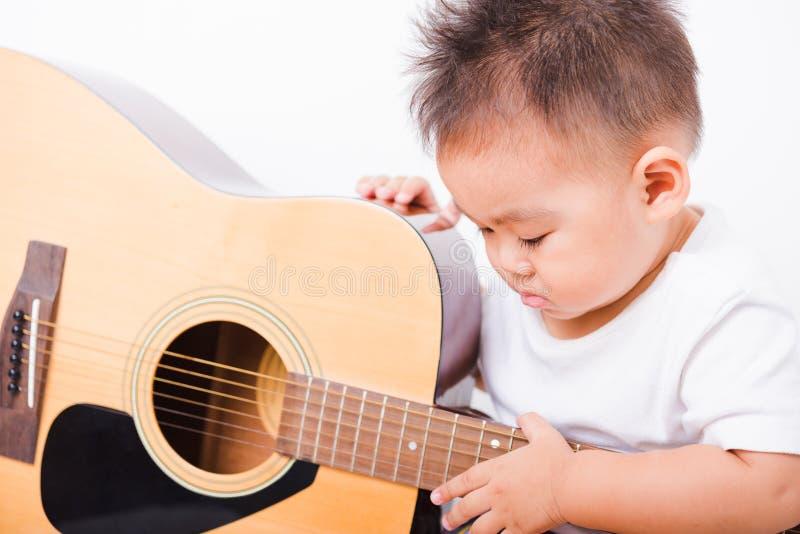 亚裔画象儿童男孩1年弹吉他的6个月 免版税库存照片