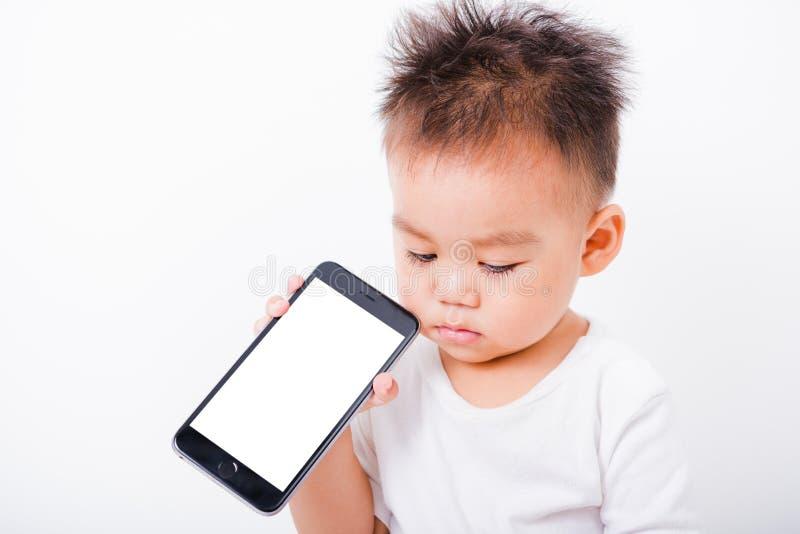 亚裔画象儿童男孩1年拿着展示智能手机黑屏的6个月 免版税库存照片