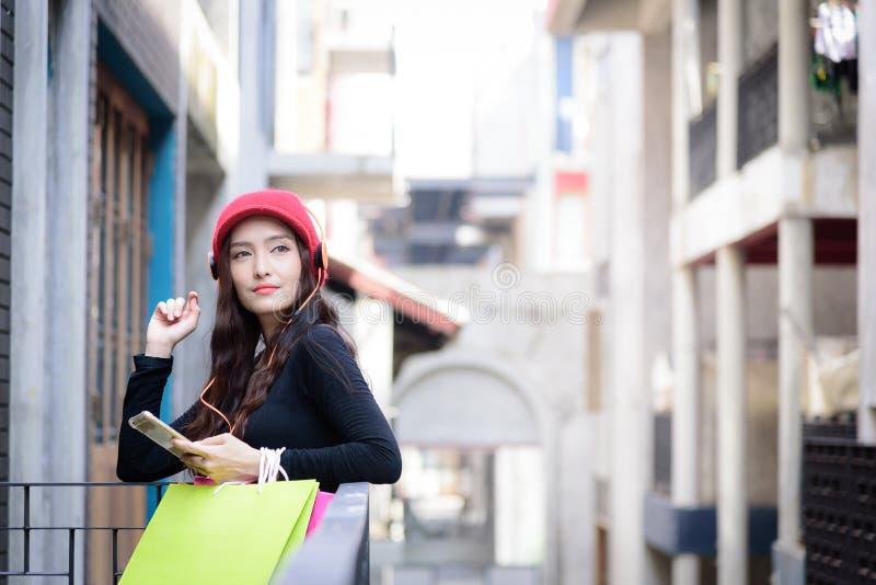 亚裔画象女孩有与购物的五颜六色的袋子的愉快和听的音乐 库存照片