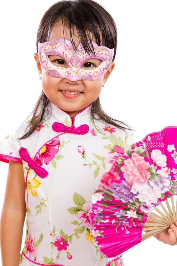 亚裔矮小的中国女孩佩带的面具和拿着东方爱好者 免版税库存照片
