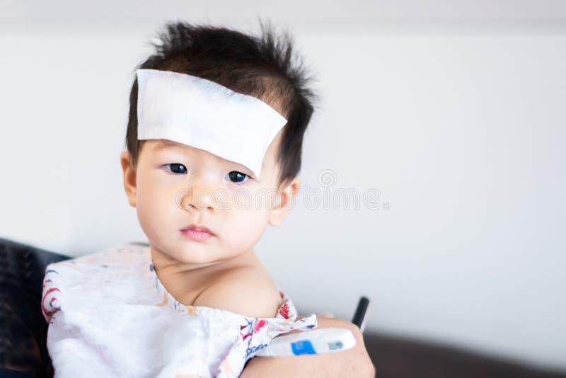 亚裔矮小的婴孩病与在前额的凉快的热病jel垫 库存图片