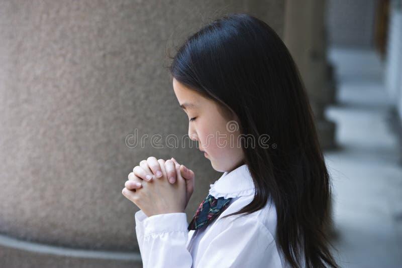 亚裔祈祷的女小学生 库存照片