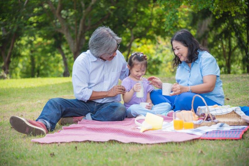 亚裔祖父母由p花费时间在与孙女的假日 免版税库存照片