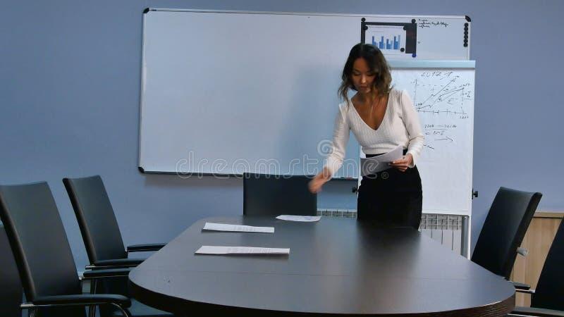 年轻亚裔秘书大厅为见面做准备,把纸放在书桌上在办公室 免版税库存图片