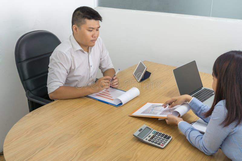 亚裔经理不同意关于想法的雇员在报告 库存图片