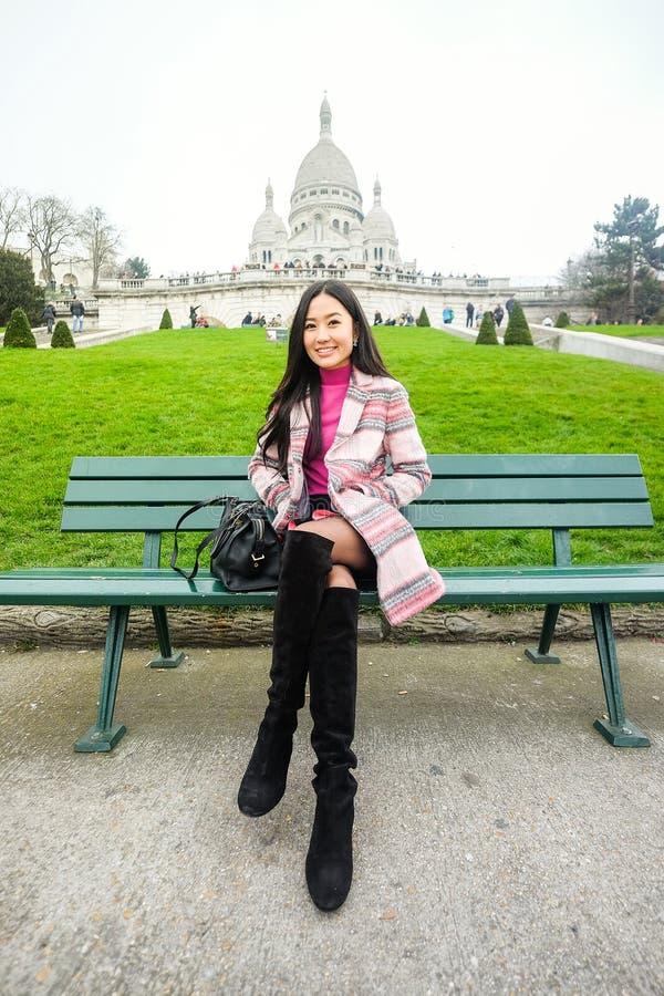 亚裔美丽的女孩坐长凳在Sacre-Coeur附近  库存图片