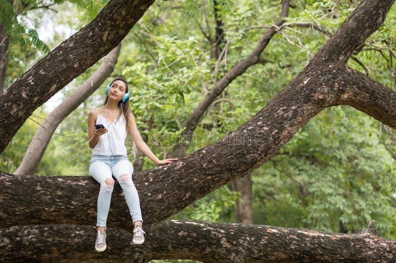 亚裔美丽的愉快的妇女坐大树并且听放出音乐 库存图片