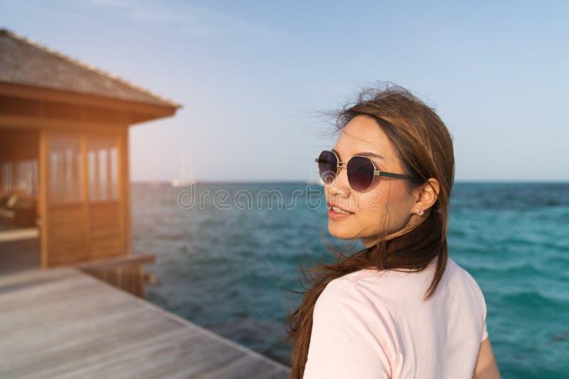 亚裔美女enjoyful旅行的海背景 免版税库存图片