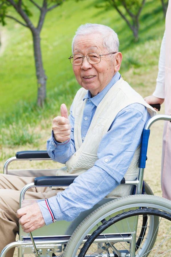 亚裔老人坐有赞许的一个轮椅 库存照片