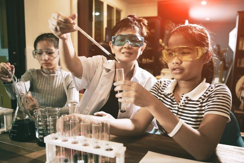 亚裔老师和学生在学校科学实验室室 库存照片