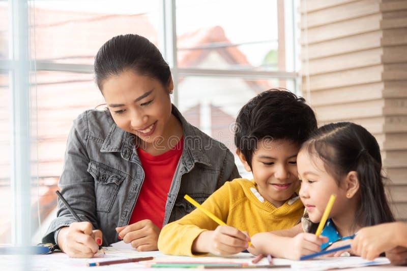 亚裔老师教的艺术和上色与小孩 免版税库存图片