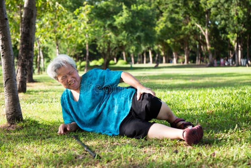 亚裔老年人用在地板上的拐棍在跌倒以后在夏天室外公园,病的资深妇女跌倒了对地板 免版税图库摄影