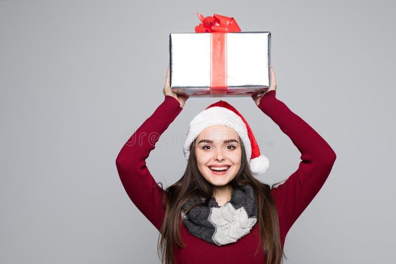 亚裔背景白种人圣诞节逗人喜爱的礼品女孩愉快的帽子藏品查出快乐的混杂的当前种族显示微笑的佩带的白人妇女年轻人的圣诞老人 戴圣诞老人帽子的微笑的愉快的逗人喜爱的少妇显示圣诞节礼物 免版税库存图片