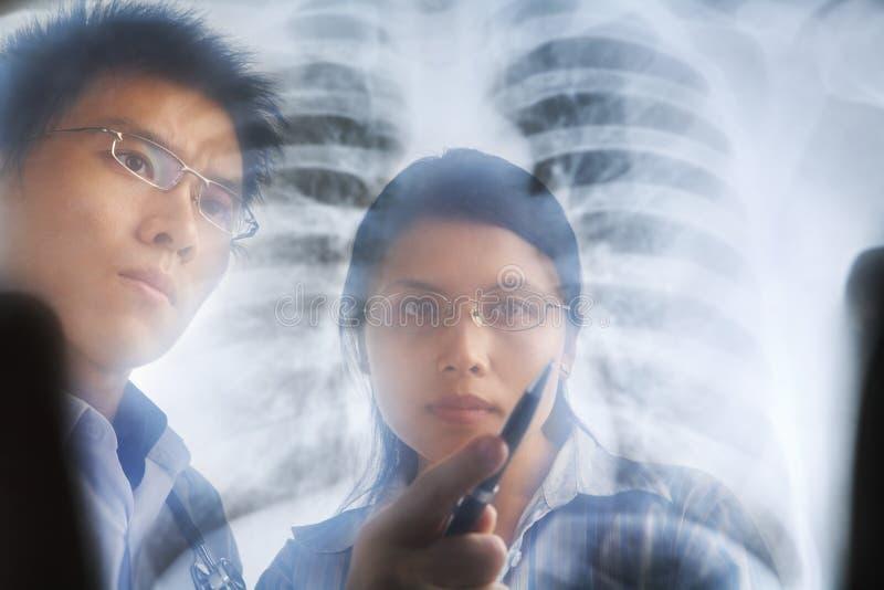 亚裔论述医生有在打印X-射线 图库摄影