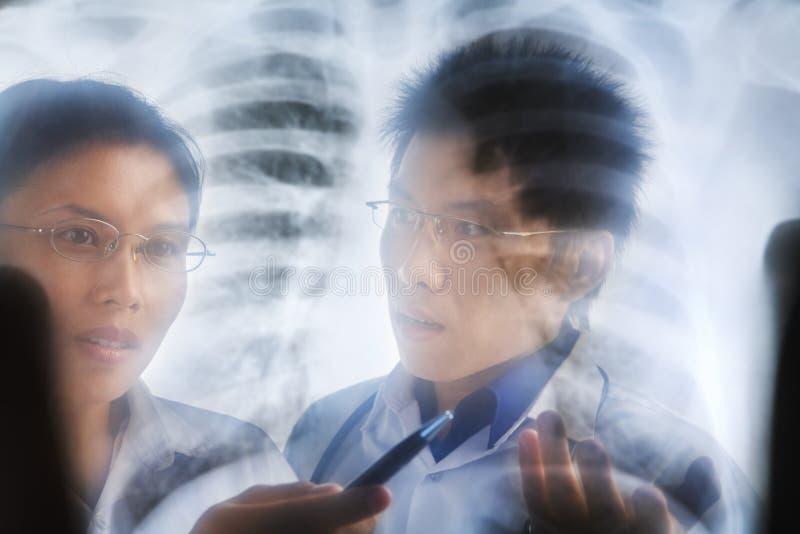 亚裔论述医生有在打印X-射线 免版税图库摄影