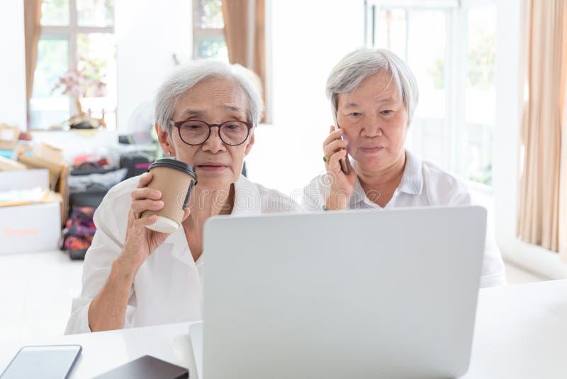 亚裔资深妇女和朋友有手提电脑的,观看事的老年人有趣,当拿着电话,谈话时 图库摄影