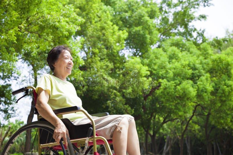 亚裔资深妇女坐轮椅 免版税图库摄影