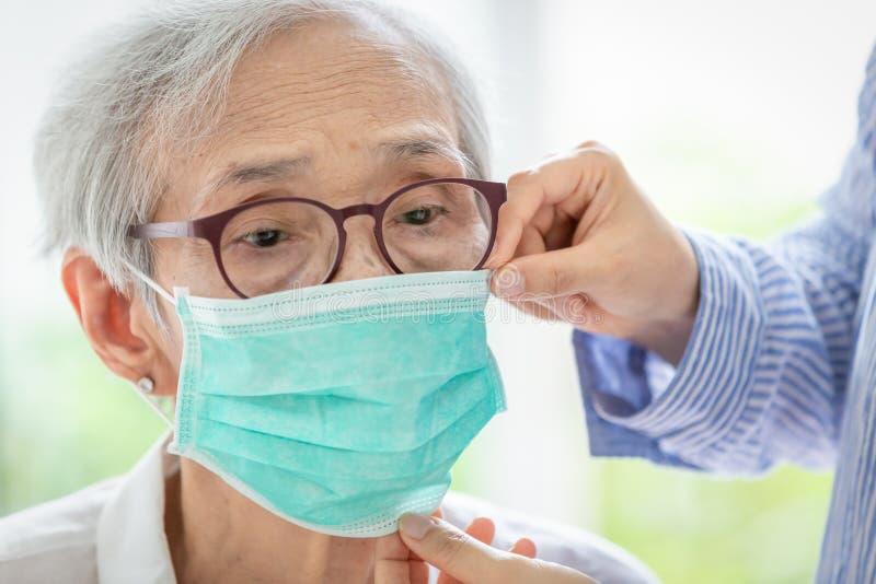 亚裔资深妇女遭受与面膜保护,年长由于空气污染,老病残的妇女佩带的面膜的咳嗽 免版税库存图片