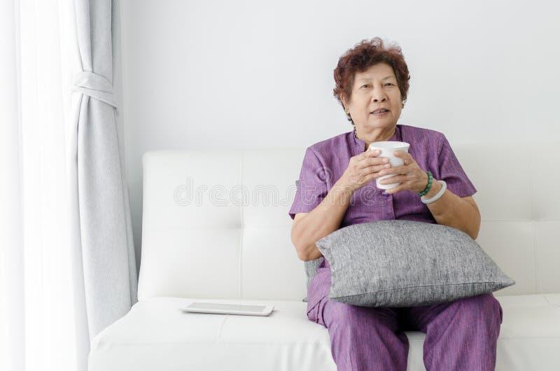 亚裔资深妇女饮用水,坐长沙发在窗口附近 免版税图库摄影