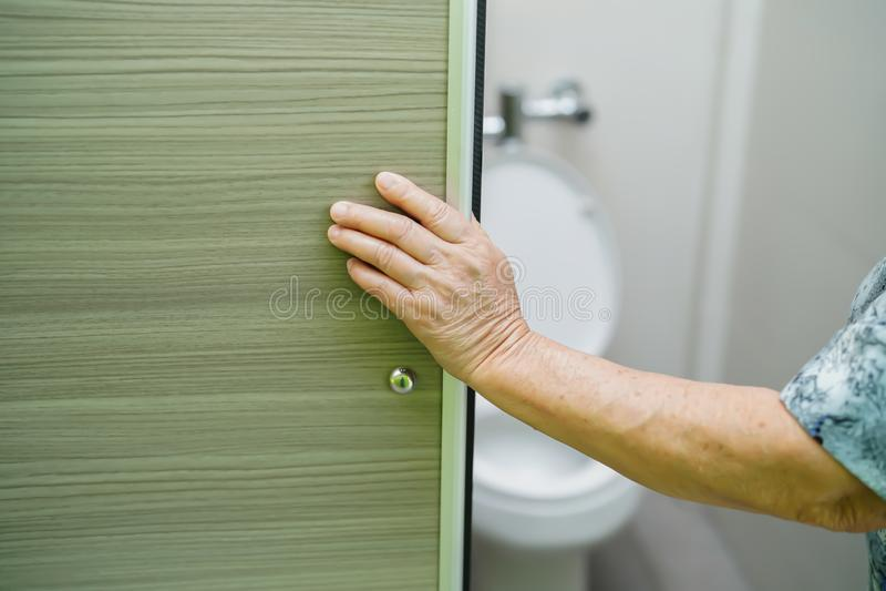 亚裔资深年长用手老妇人妇女耐心开放洗手间卫生间幻灯片门 图库摄影