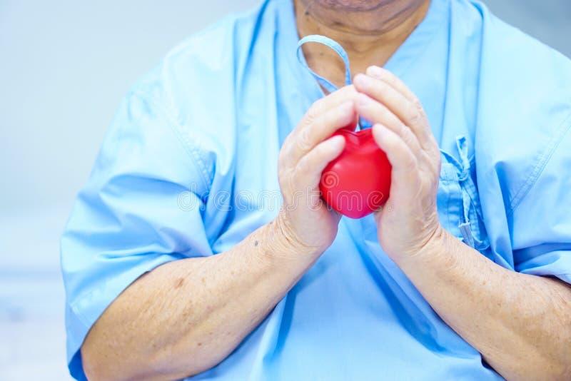 亚裔资深或年长老妇人妇女患者在她的手上的拿着红色心脏在床上在护理医院 免版税库存图片