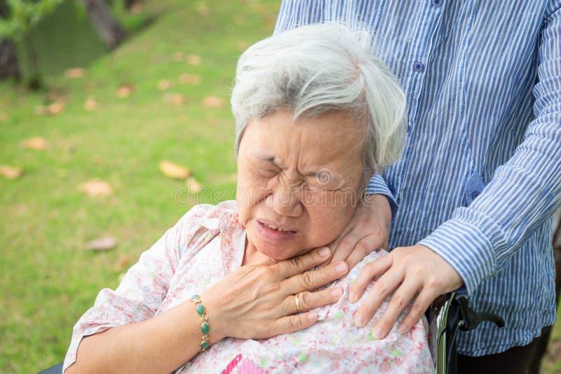 亚裔资深母亲有神经痛苦、肩膀和脖子痛、按摩她的肩膀年长妇女的女性照料者或者女儿, 库存图片