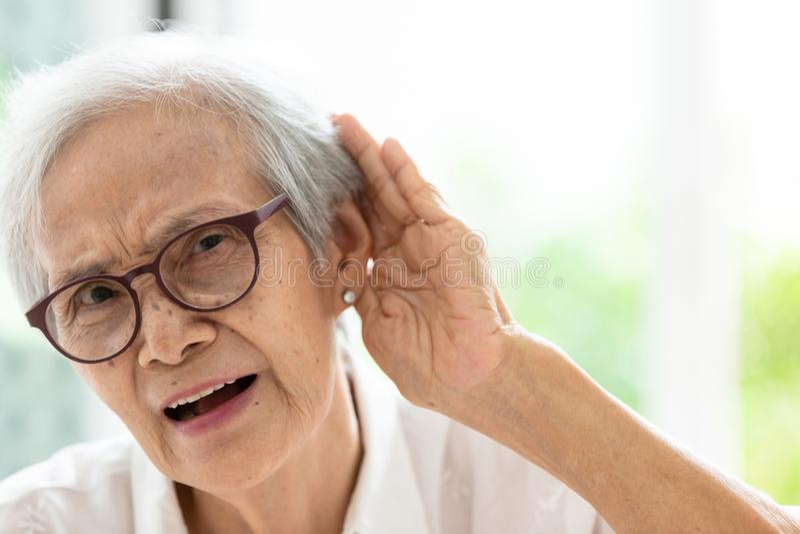 亚裔资深由耳朵决定的妇女听的by hand的,有听见的困难在听力,年长妇女艰苦,戴眼镜与 库存照片