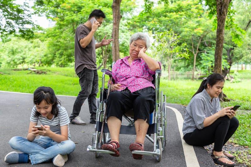 亚裔资深祖母将从家庭,年长乏味,哀伤,沮丧,无视,父母,有互联网的儿童女孩忽略, 库存图片