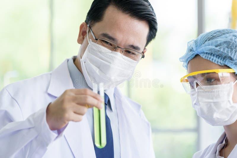 亚裔资深科学家有教的年轻学生科学家在实验室 库存照片