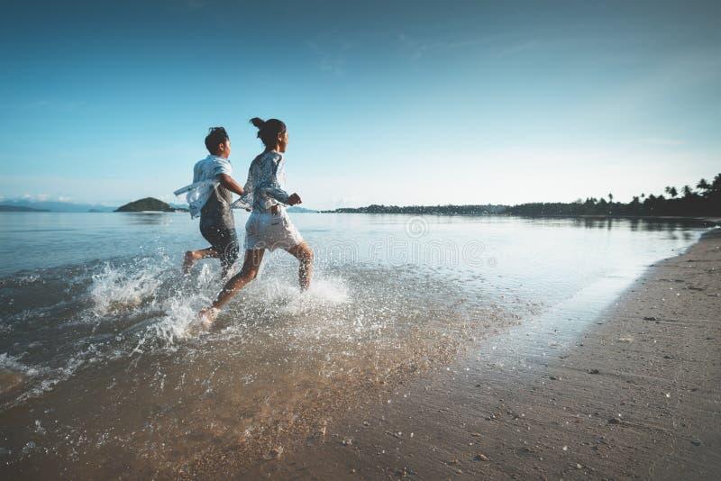 亚裔跑在海滩的十几岁的女孩和男孩 免版税库存照片