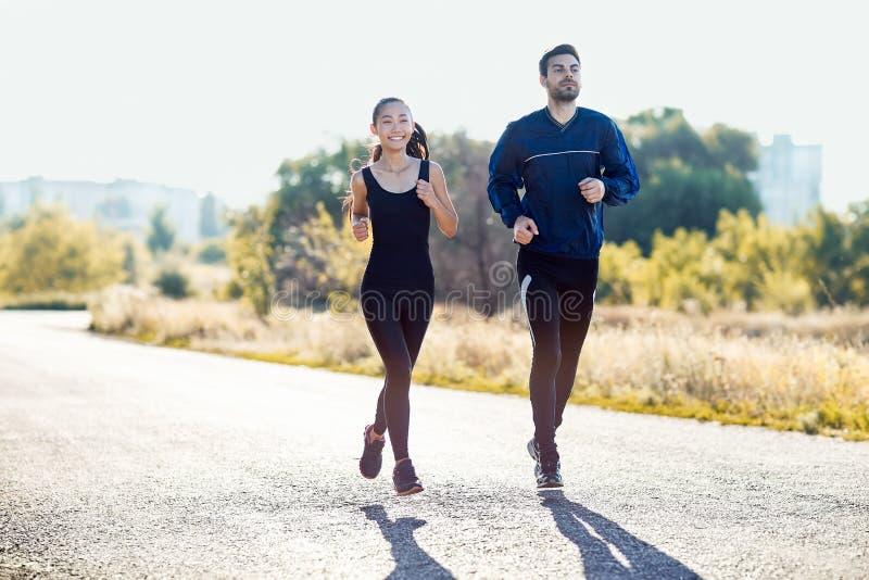 亚裔跑步在晴天的妇女和白种人人 图库摄影