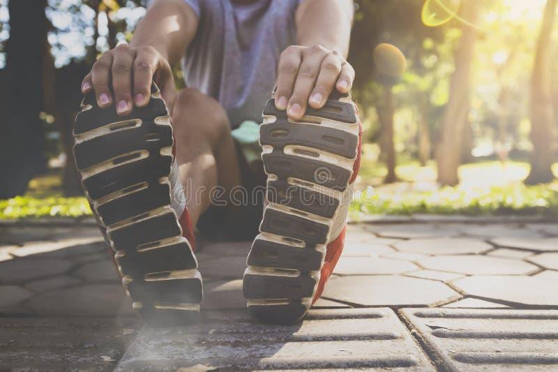 亚裔运动员在跑前在路舒展他的腿解决在公园 图库摄影