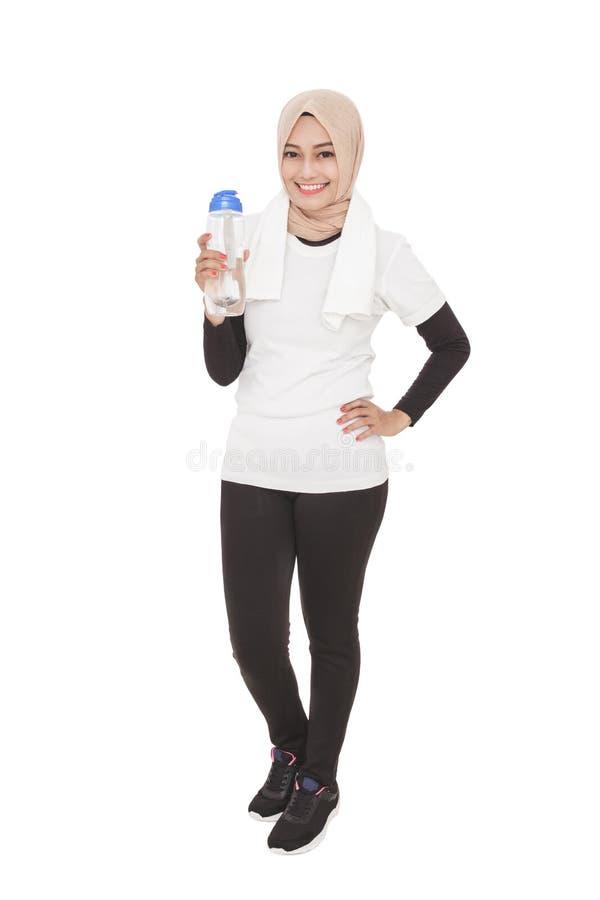 亚裔运动的拿着一个瓶矿物wat的妇女佩带的hijab 免版税库存图片