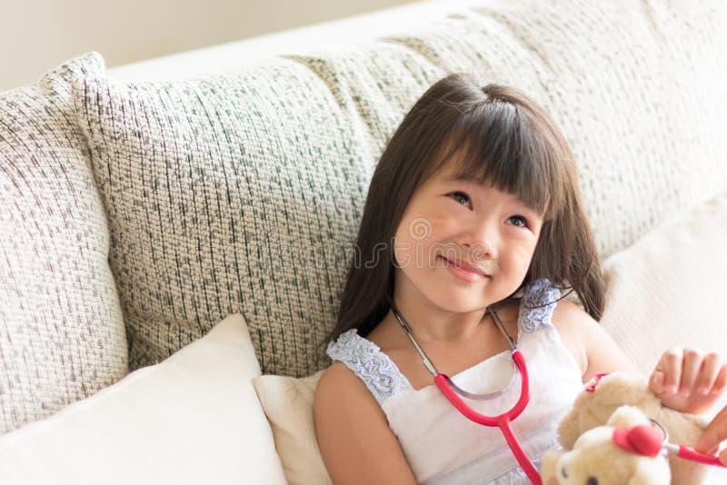 亚裔逗人喜爱的小女孩是微笑和扮演有stetho的医生 免版税图库摄影