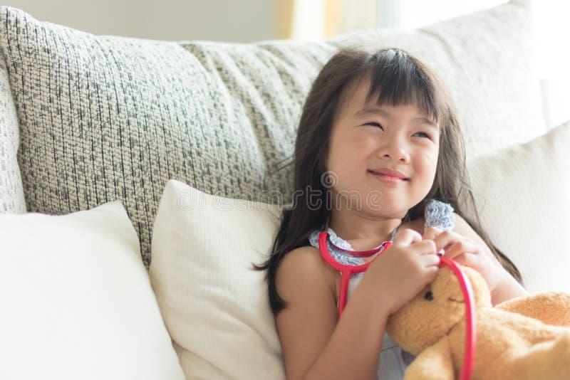 亚裔逗人喜爱的小女孩是微笑和扮演有stetho的医生 库存图片