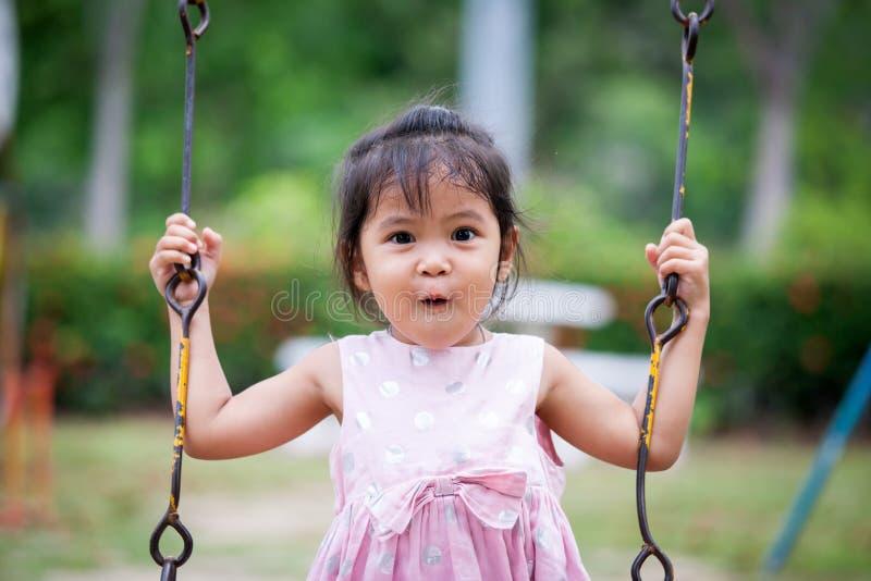 亚裔逗人喜爱的小女孩的惊奇的面孔,当演奏摇摆时的她 免版税库存图片