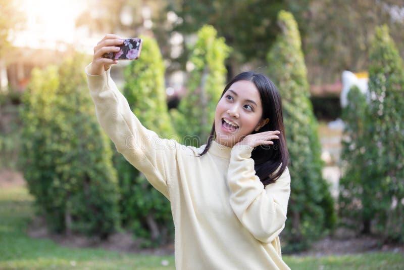 亚裔采取照片和Selfie在松弛钛的妇女愉快的微笑 免版税图库摄影