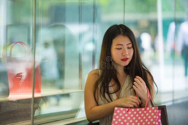 亚裔韩国愉快的走在街道上的妇女运载的购物袋在衣物窗口商店旁边在买在femal的秀丽材料以后 图库摄影