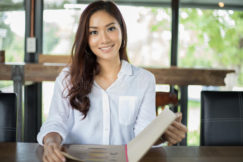 亚裔预定的妇女开放菜单在咖啡咖啡馆和餐馆 库存照片