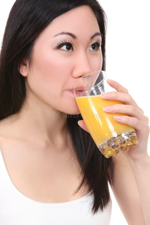 亚裔饮用的汁液桔子妇女 库存照片