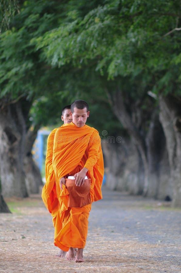 亚裔年轻修士走的早晨施舍 免版税图库摄影