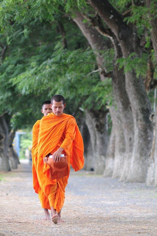 亚裔年轻修士走的早晨施舍 免版税库存图片