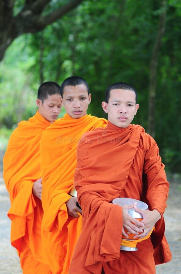 亚裔年轻修士走的早晨施舍 免版税库存照片